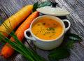 Carrot soup on wooden background Stock Images