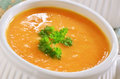 Carrot sweet potato soup creamy and with parley garnish in white ribbed bowl Royalty Free Stock Photos