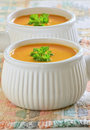 Carrot sweet potato soup creamy and with parley garnish in white ribbed bowls Stock Photos
