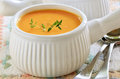 Carrot sweet potato soup creamy and with sprig of thyme in white ribbed bowl Royalty Free Stock Photography