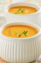 Carrot sweet potato soup creamy and with sprig of thyme in white ribbed bowls Royalty Free Stock Image