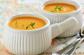 Carrot sweet potato soup creamy and with sprig of thyme in white ribbed bowls Stock Photo