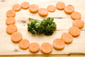Carrots in heart form and parsley on cutting edge board Royalty Free Stock Photography