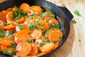 Carrots and sour cream in a frying pan with herbs closeup Stock Photography