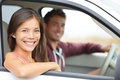 Cars couple driving in new car smiling happy looking at camera young people on road trip drive beautiful interracial Royalty Free Stock Photography