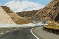 Cars on serpentine road driving up through the mountains Royalty Free Stock Images