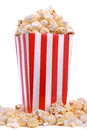 Carton of fresh popcorn overflowing red and white striped box Royalty Free Stock Images