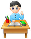 Cartoon boy learning at table giving thumbs up Royalty Free Stock Photo