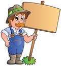 Cartoon farmer holding wooden board Stock Images