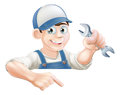 Cartoon mechanic peeking over sign a plumber or with a wrench or banner and pointing at it Royalty Free Stock Photography