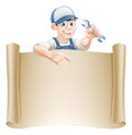 Cartoon mechanic and scroll a or plumber holding an adjustable spanner or wrench peeking over a sign pointing Stock Photography