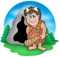 Cartoon prehistoric man before cave Royalty Free Stock Image
