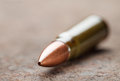 Cartridge on rusted iron background macro of kalashnikov bullet over corroded plate Stock Photo