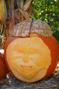 Carved pumpkin face with a brain shaved and winking made out of another squash Stock Photo