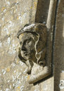 Carved stone figure head on window surround st marys norman church beverston gloucestershire Stock Image
