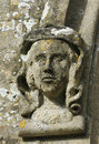 Carved stone figure head on window surround st marys norman church beverston gloucestershire Royalty Free Stock Photo