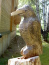 Carved wooden figure of a crow on tree stump Stock Photos