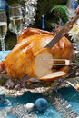 Carving roasted turkey for white christmas garnished with herbs on blue decorations and champagne tree as background Stock Photography