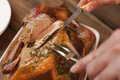 Carving a tasty thanksgiving roast turkey closeup view from above of man slicing the breast with knife Royalty Free Stock Photo