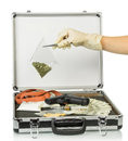 Case with money and drugs silver gun on black background Royalty Free Stock Images
