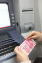 Cash at atm female hands with one hundred yuan chinese banknotes Royalty Free Stock Photo