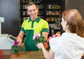 Cashier in retail store serving client or shopkeeper flower shop or a customer Royalty Free Stock Images