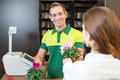 Cashier in retail store serving client or shopkeeper flower shop or a customer Royalty Free Stock Photography
