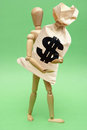 Cashout a wooden guy holds onto a large bag of money for many financial concepts Royalty Free Stock Photography