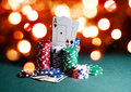 Casino chips and cards, two aces on the playing green table against bright bokeh lights. Poker game theme backdrop Royalty Free Stock Photo