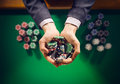 Casino playes holding a handful of chips elegant male player with green table on background hands close up top view Stock Photography