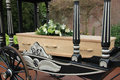 Casket on a funeral carriage wooden with flowerson Royalty Free Stock Image