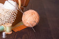 Casket with needlework and beige skein of thread spokes for knitting on a wooden table Stock Photo