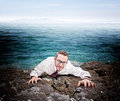 Castaway businessman climb the cliff Stock Photo