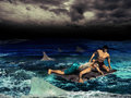 Castaways two men in the middle of the ocean on a wooden board surrounded by sharks Royalty Free Stock Photos
