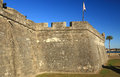Castillio san marcos fortress walls in st augustine florida with canon aimed at the town with spanish flag Royalty Free Stock Images