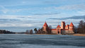 Castle of trakai in the winter at the sunset with frozen lake in the foreground Stock Photos