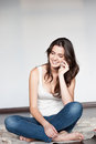 Casual brunette young woman white singlet jeans sitting wool plaid talking cell phone Royalty Free Stock Image