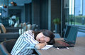 Casual Business Asian taking a nap in front of laptop, sleeping Royalty Free Stock Photo