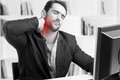 Casual businessman with pain in his neck sitting a desk black and white red dot around painful area Stock Photos