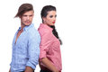 Casual couple back to back looking in same way young standing and the direction away from the camera on white background Stock Photos