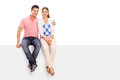 Casual couple posing seated on a blank panel isolated white background Stock Photo