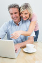 Casual couple using laptop at home concentrated content Stock Photos