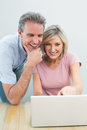 Casual couple using laptop at home concentrated content Stock Photo