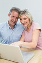 Casual couple using laptop at home concentrated content Stock Image