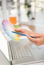 Casual designer working with laptop and colour chart in the office Royalty Free Stock Images