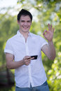 Casual dressed young student texting on cell phone outdoor smiling Royalty Free Stock Photos