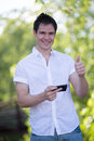 Casual dressed young student texting on cell phone outdoor smiling Royalty Free Stock Images