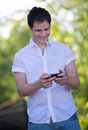 Casual dressed young student texting on cell phone outdoor smiling Stock Photography
