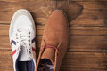 Casual and dressy mens shoes on wooden table Stock Photos