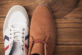 Casual and dressy mens shoes on wooden table Stock Image